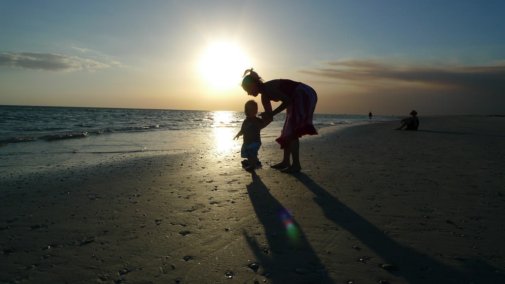 Чернокожая (на вид 15-летняя) девочка с годовалым ребенком на руках